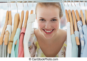 Happy female customer amid clothes rack - Close-up portrait ...