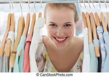 Happy female customer amid clothes rack - Close-up portrait...
