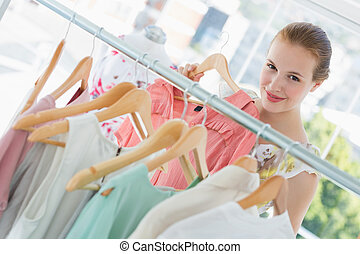 Happy female customer selecting clothes in store - Close-up...