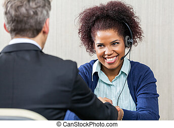 Happy Female Customer Service Agent Shaking Hands With Manager