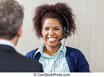 Happy Female Customer Service Executive Looking At Manager