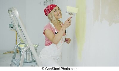 Happy female dipping brush in wall paint - Beautiful young...