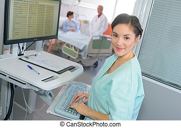 happy female doctor at the computer in hospital room