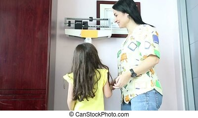 Happy female doctor checking girl's weight