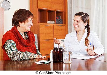 happy female doctor prescribing medication to mature woman