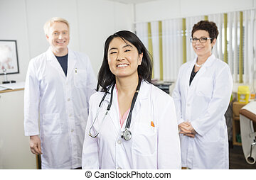 Happy Female Doctor Standing With Colleagues