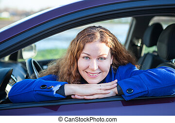 Happy female driver in car window with clasped hands looking at camera