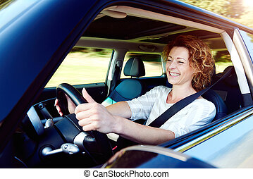 Happy female driver steering car with safety belt