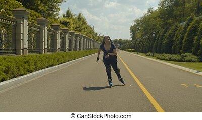 Happy female enjoying speed and wind rollerblading - Joyful...