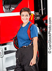 Happy Female Firefighter Standing Against Firetruck