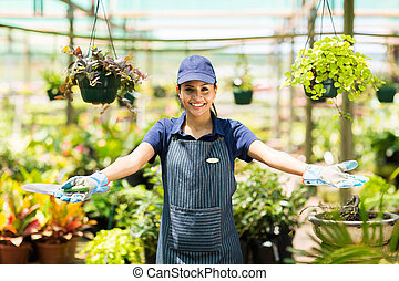 happy female florist portrait in greenhouse with welcome gesture