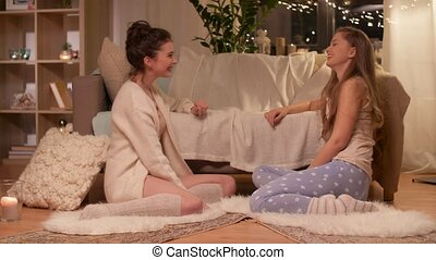 happy female friends at home pajama party