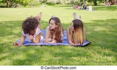 Happy female friends lying on grass - Group of cheerful...