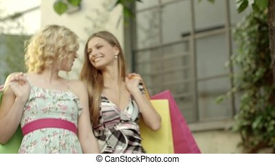 Happy female friends smiling, bags