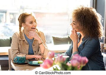 Happy female friends speaking in cafe