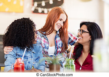 happy female friends with drinks at bar