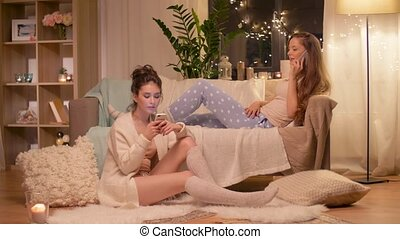 happy female friends with smartphones at home