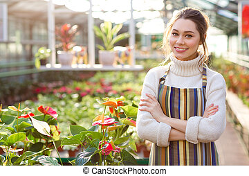 Happy female gardener standing near flowers of anthuriums in greenhouse