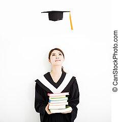 happy female graduate looking the graduation cap in air