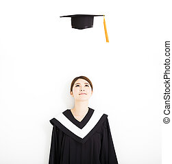 happy female graduate looking the graduation cap in air