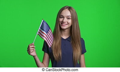 Smiling girl holding small USA flag and showing thumb up hand gesture at the end, over green chroma key background