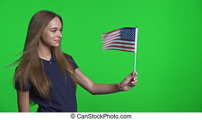 Smiling girl holding USA flag and and watching it fluttering on wind, over green chroma key background