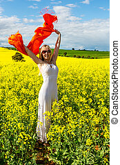 Happy female in field of golden flowers, zest for life