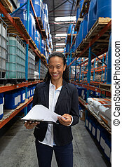 Happy female manager writing on clipboard in warehouse - ...