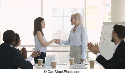 Happy female mature boss handshaking young employee...