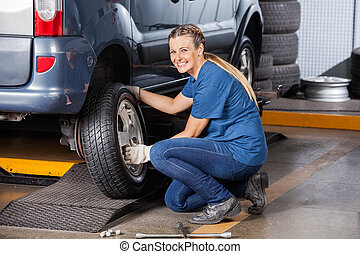Happy Female Mechanic Adjusting Car Tire