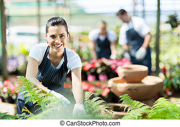 nursery worker trimming plants - happy female nursery worker...