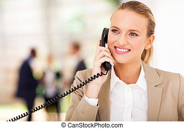 office worker talking on landline phone - happy female...