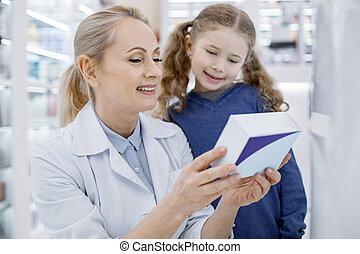 Happy female pharmacist and girl reading