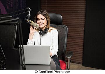 Happy female radio broadcaster hosting a live show