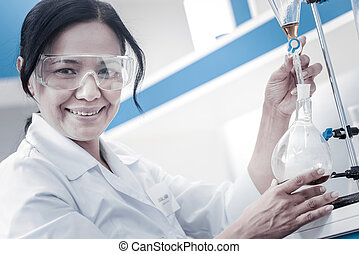 Happy female researcher smiling while pouring liquid into flask