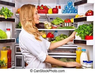Happy female search something in the fridge, fresh fruits...