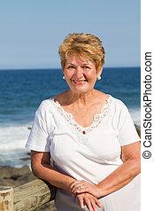 happy female senior citizen on beach