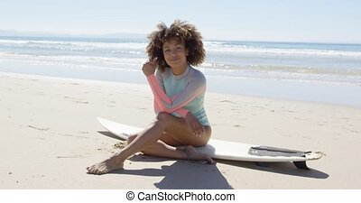 Happy female sitting on a surfboard