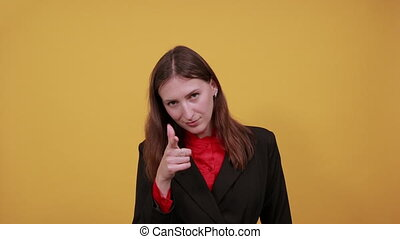 Young Attractive Brunette Woman In Black Stylish Suit, Red Shirt On Yellow Background, Happy Female Smile Shows Forward Forefinger. The Concept Of Confident People, Leaders