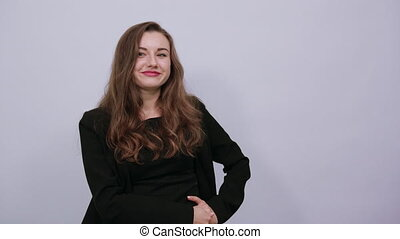 Young Attractive Woman Brunette In In A Black T-Shirt And Sweater On White Background, Happy Female Smiling Shows On Camera Forefinger. The Concept Is Accuse, Show, Of Human Guilt
