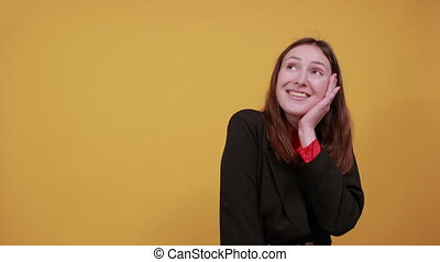 Young Attractive Brunette Woman In Black Stylish Suit, Red Shirt On Yellow Background, Happy Female Smiling Touches Palms Her Hands To Chin. The Concept Of Successful, Kind People