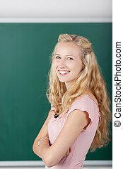 Happy Female Student Against Chalkboard