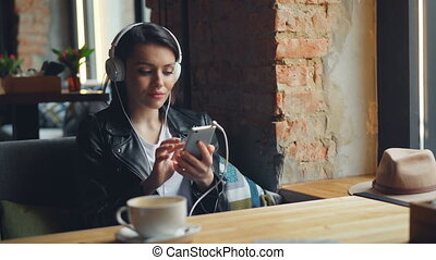 Happy female student is listening to music in headphones using smartphone in cafe enjoying lunch break alone. Modern technology and youth culture concept.