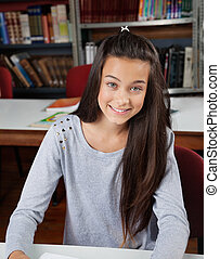 Happy Female Student Sitting In Library