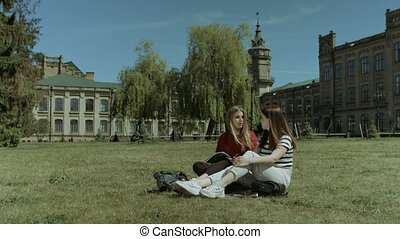 Happy female students relaxing on campus lawn