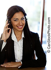 Happy female support phone operator in headset at workplace
