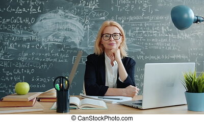 Happy female teacher smiling looking at camera at desk in class with chalkboard wall