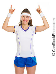 Happy female tennis player pointing up on copy space
