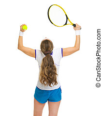 Happy female tennis player rejoicing success. rear view