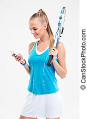 Happy female tennis player using smartphone